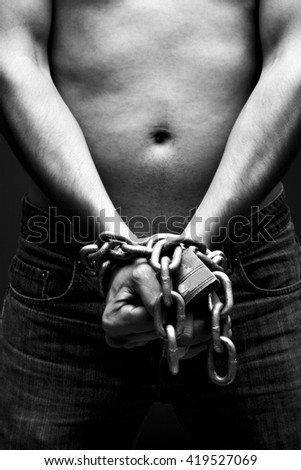 Chain hands of a man on black background - stock photo