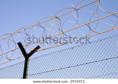 Chain link fence and barbed wire against blue sky - stock photo