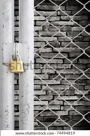 Chain link fence and metal door with lock see grunge wall background - stock photo