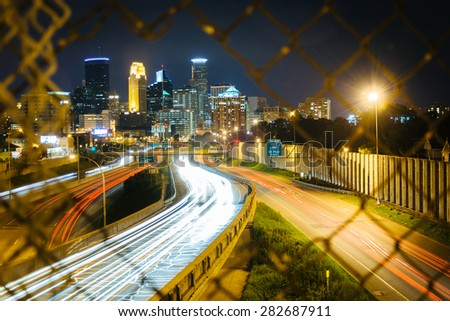 Chain link fence and view of I-35 and the skyline at night, seen from the 24th Street Pedestrian Bridge, in Minneapolis, Minnesota.