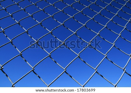 chain link fence mesh with blue sky background - stock photo