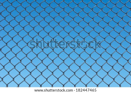 Chain Link Fence with a Blue Sky Background - stock photo