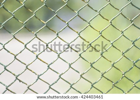 Chain link fence with a green background - stock photo