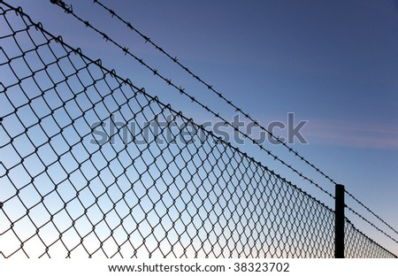 Chain link fence with barbed wire against evening sky - stock photo