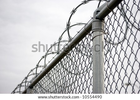 Chain link fence with razor wire on top - stock photo