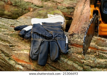 Chain saw and protective gloves. Wood background.