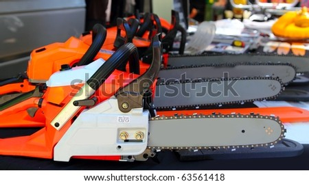 chain saw machines row perspective in shop tools market - stock photo
