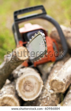 Chain saws cut logs in nature. - stock photo
