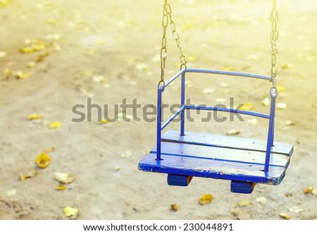 Chain swing on kids playground in autumn - stock photo