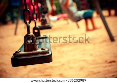 chain swings on playground with blur kid on park , vintage tone color - stock photo