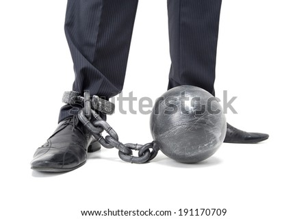 Chained Feet. A businessman restrained by ball and chain. - stock photo