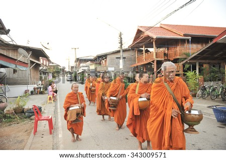 chaingkhan in loie province, Thailand - november 17 :street life in chaingkhan in loie province on november17, 2015. give alms to a Buddhist monk sticky rice - stock photo