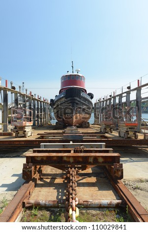 Chains and gear used to pull a massive tug boat out of the water onto a dry dock for repairs and maintenance
