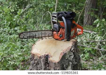 Chainsaw on a stump of a recently sawed down tree - stock photo