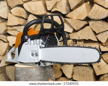 Chainsaw on stack woodpile background isolated - stock photo