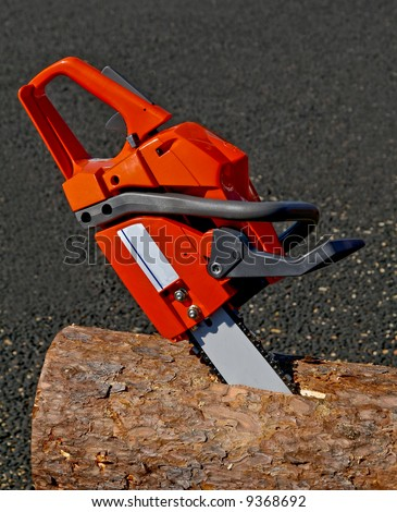 chainsaw stuck in the trunk of a tree - stock photo