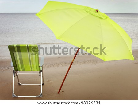 chair and green umbrella on the beach - stock photo