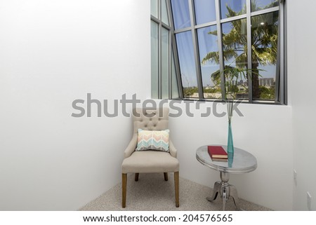 Chair and small table in hallway with large view window - stock photo