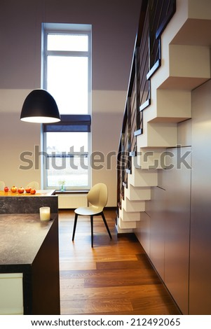 Chair and staircase in modern house interior - stock photo