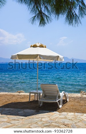 Chair and umbrella at greek beach - vacations background - stock photo