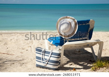 chair beach bag and hat by the sea - stock photo