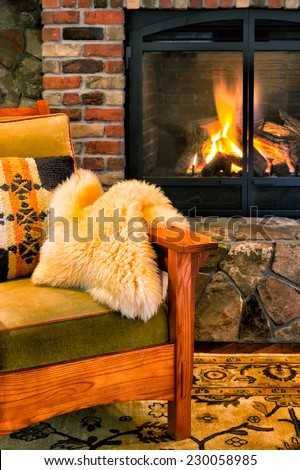 Chair by a cozy fireplace with a crackling fire. Gas insert with a glass screen. Style is rustic elegance, lodge, arts and crafts, upscale cabin. - stock photo