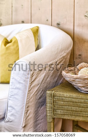 Chair in a white slipcover with a striped pillow next to a green wicker side table with a basket of shells. Comfortable, casual seaside cottage decor. - stock photo