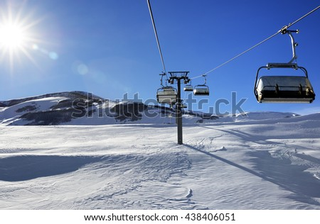 Chair-lift and blue sky with sun and sunbeams. Greater Caucasus, Mount Shahdagh. Qusar rayon of Azerbaijan. - stock photo