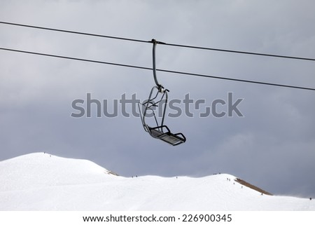 Chair lift and off-piste slope at gray day. Caucasus Mountains, Georgia, ski resort Gudauri. - stock photo
