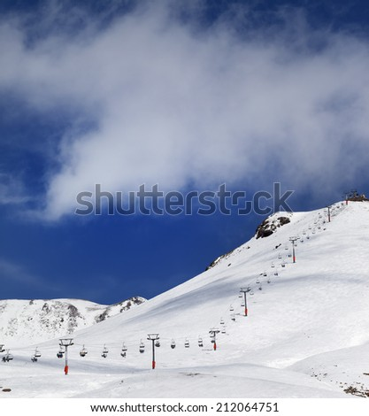 Chair-lift and ski slope in sun day. Caucasus Mountains, Georgia. Ski resort, Gudauri. - stock photo