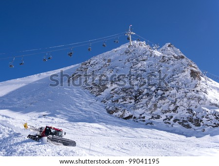 Chair lift and snow groomer at Hintertux Glacier in Zillertal Alps in Austria - stock photo