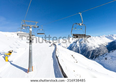 Chair lift hovering above the ski slopes at the Austrian ski resort Soelden.