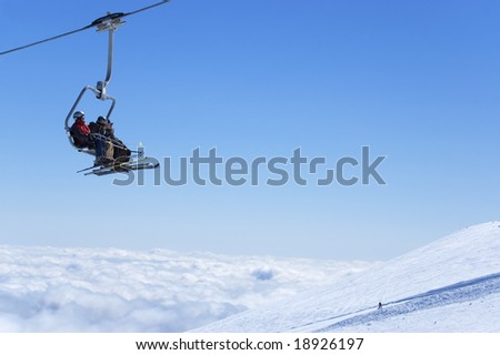 Chair lift with skiers at ski resort above the clouds. Snowboarder on the slope. - stock photo