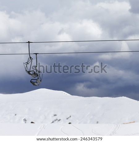 Chair lifts and off-piste slope at windy gray day. Caucasus Mountains, Georgia. Ski resort Gudauri. - stock photo