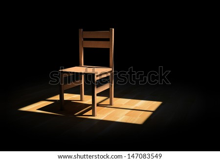 Chair on a dark room illuminated only by a light coming from a window - stock photo