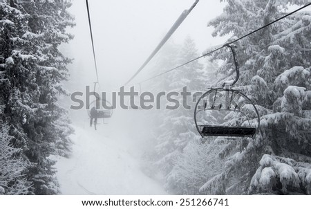 Chair ski lift in misty snowy alpine forest in Chamonix, French Alps - enigmatic winter background  - stock photo