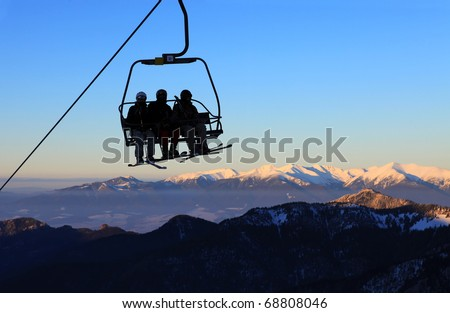 Chair ski lift with skiers over blue sky and mountains - stock photo