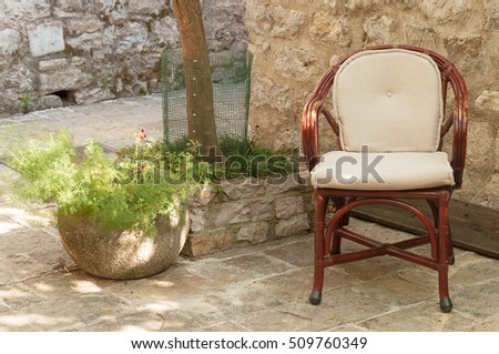 Chair under tree in patio in old town of Budva, Montenegro.