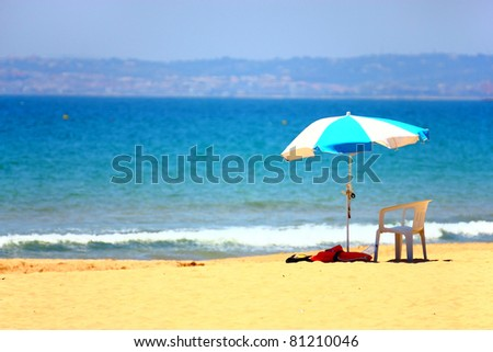 Chair under umbrella on beautiful beach in Portimao, Portugal - stock photo