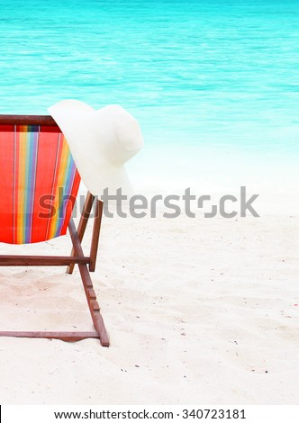 chair with a hat on the beach - stock photo