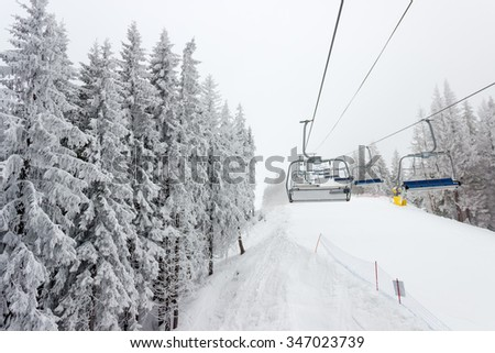 Chairlift and ski piste among the spruce forest at ski resort in cloudy weather