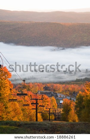 Chairlift on a brightly lit mountain slope with spectacular morning mist in the valley - stock photo