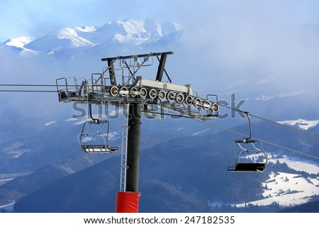 Chairlift on winter ski resort with mountain Background - stock photo