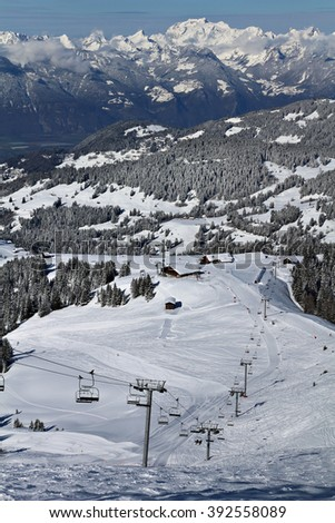 Chairlifts transport skiers and snowboarders up a slope at a winter ski resort in the Alps.  - stock photo