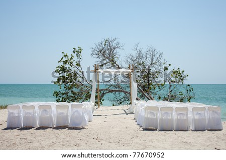 Chairs and a chuppa on a beach for a wedding - stock photo