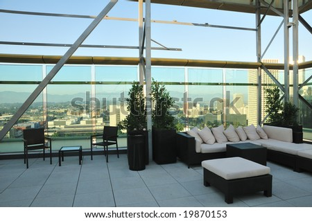 Chairs and a couch provide a place to enjoy the downtown sunset from a highrise rooftop