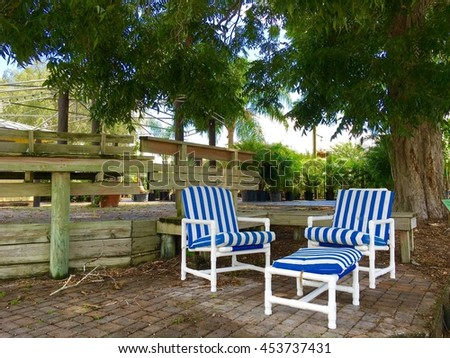 Chairs and blue pillow under  the big tree set up for relaxing - stock photo