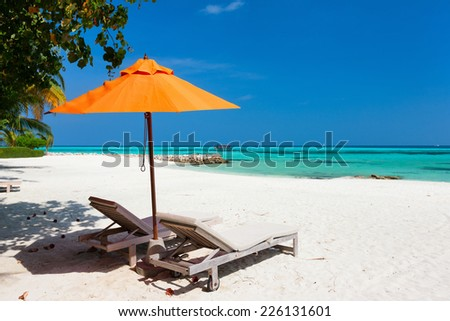 Chairs and orange umbrella on a beautiful tropical beach at Maldives - stock photo