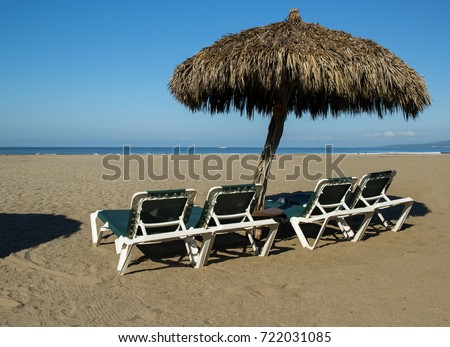 Chairs And Palm Tree Umbrella On The Beach. Puerto Vallarta, Mexico.