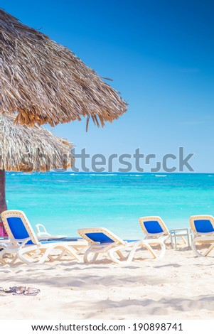 chairs and straw umbrellas on stunning tropical beach in dominican republic, punta cana - stock photo